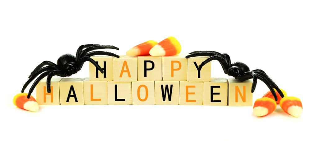 Happy Halloween wooden blocks with toy spider and candy corn isolated on a white background